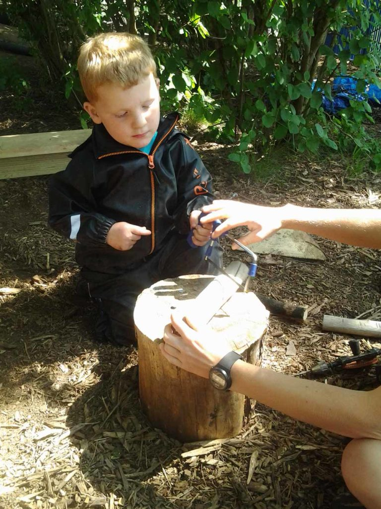 boy sawing wood - new skills are one of the benefits of forest school